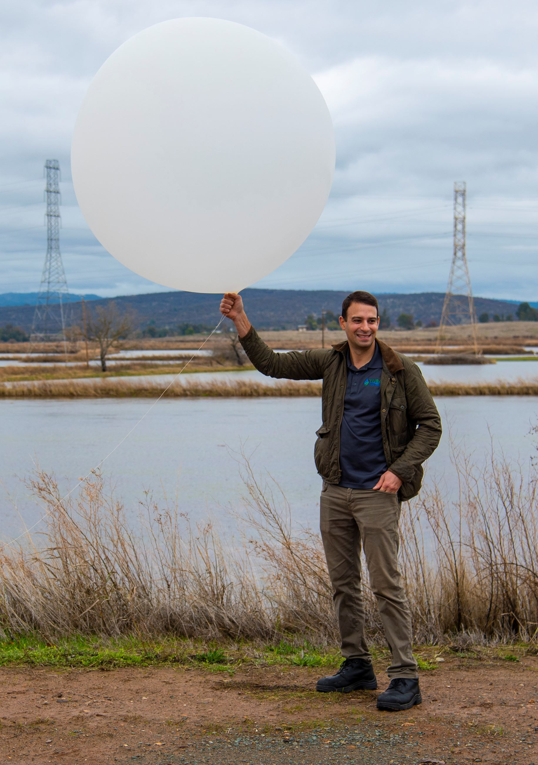 A Yuba Water Agency employee holds up a large weather balloon in front of flooded rice fields