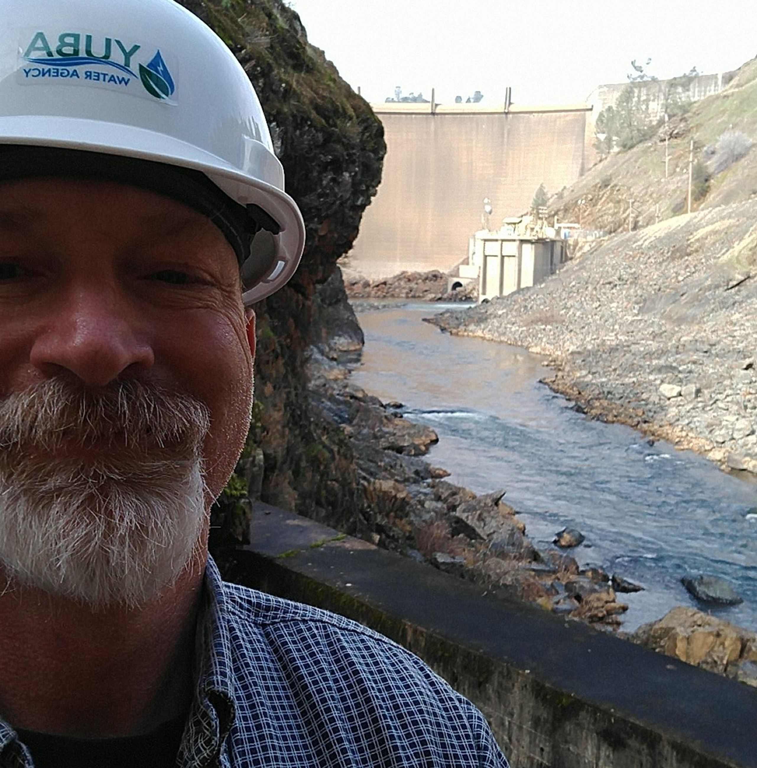 Yuba Water Agency employee Jason Newton stands with his hard hat on next to the Yuba River with Engl