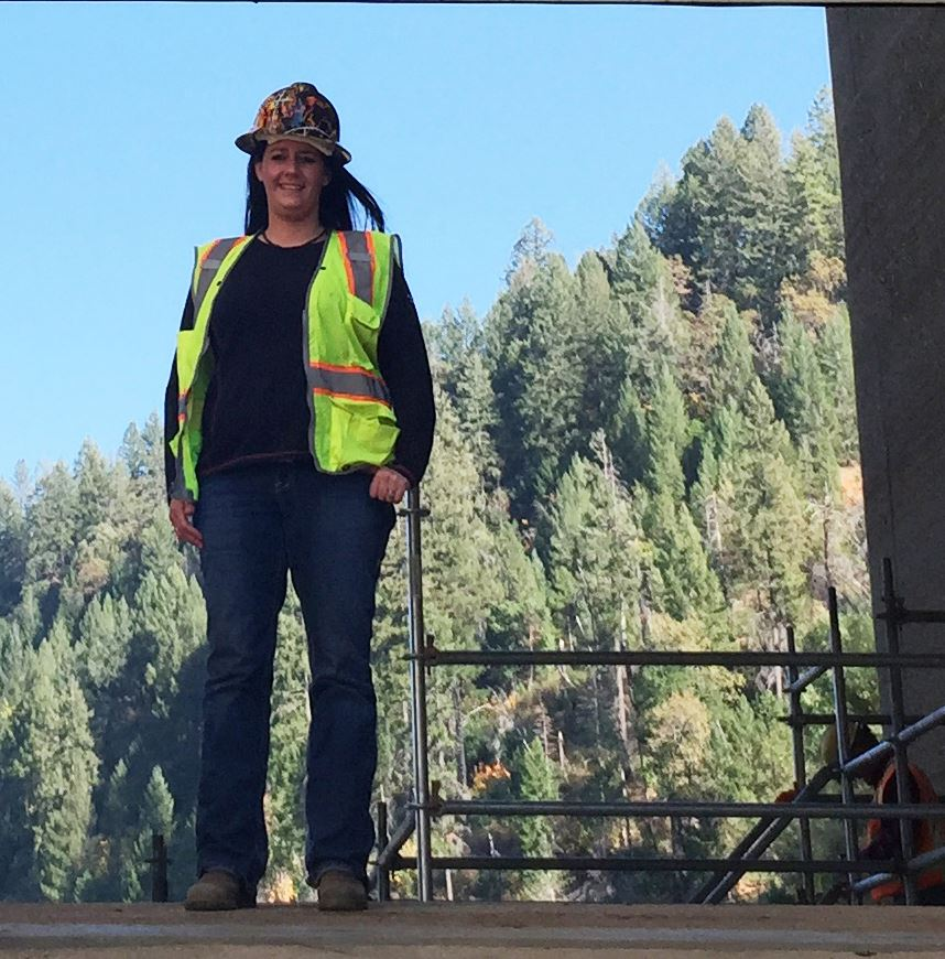 A photo of Power Systems Administrative Technician Jamie Coleman standing on a concrete structure