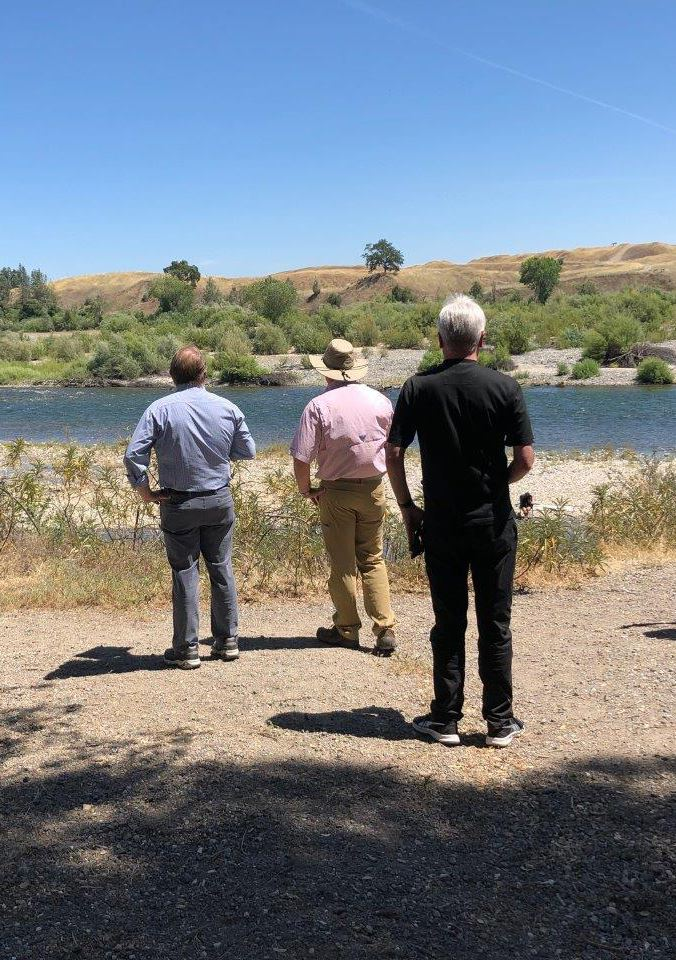 A photo of three men looking out at the Yuba River from the banks.