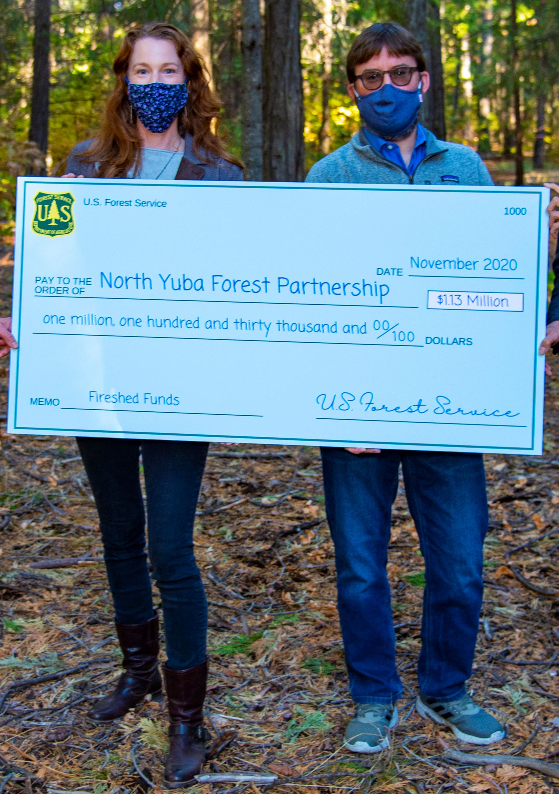 Two people wearing masks hold up a giant check from the US Forest Service.