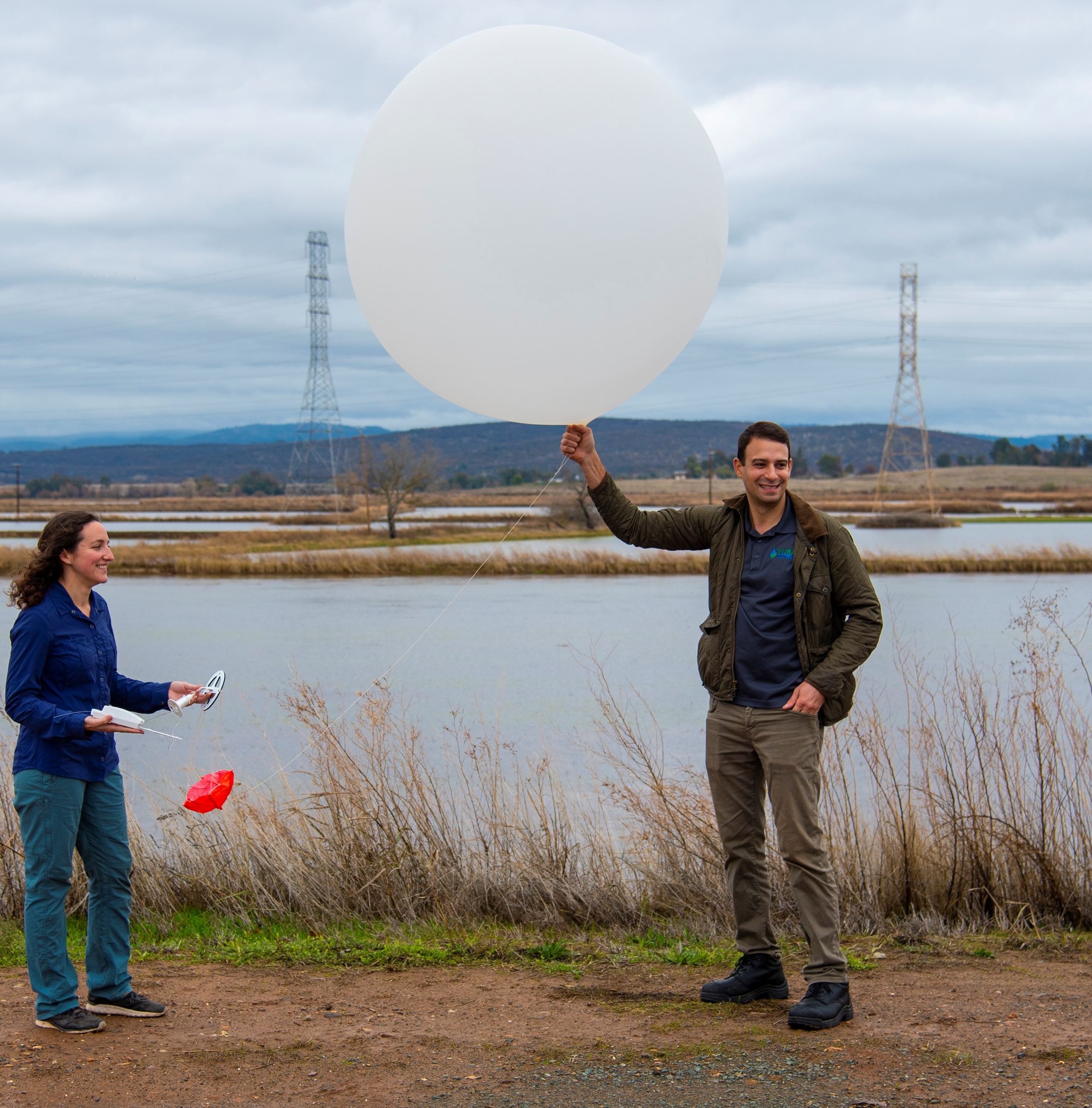 A man holds a weather balloon as he stands next to a woman holding a sensor.